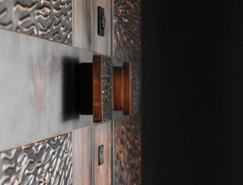 Rivestimento porta blindata in rame e bronzo.